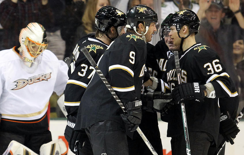 Philip Larsen of the Dallas Stars celebrate a goal in front of Jonas Hiller